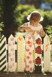 La bambina dipinge il recinto Fotografie Stock Libere da Diritti
