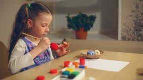 La bambina dipinge le uova di Pasqua stock footage