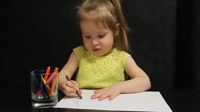 La bambina disegna con la matita marrone su carta video d archivio