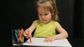 La bambina disegna con la matita rossa su carta stock footage