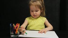 La bambina disegna con la matita verde su carta video d archivio