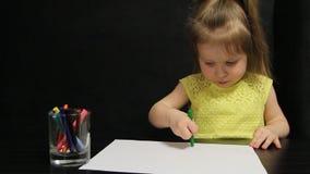 La bambina disegna con la matita verde su carta stock footage