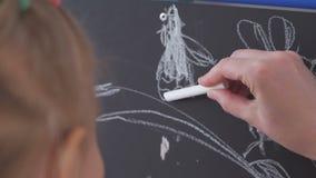 La bambina disegna il gesso bianco su un tavolo da disegno stock footage
