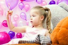 La bambina divertente attentamente considera la lecca-lecca fotografia stock