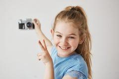 La bambina divertente con gli occhi azzurri ed i capelli leggeri sorride, tenendo il photocamera in sua mano, mostrando il v-segn immagini stock libere da diritti