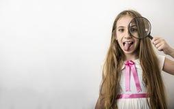 La bambina divertente e sveglia mostra la sua lingua con la lente d'ingrandimento immagini stock libere da diritti