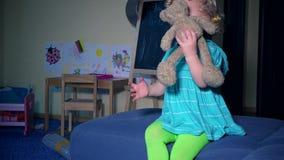 La bambina divertente racconta la storia per l'orsacchiotto della peluche del migliore amico Bambino impressionabile stock footage