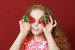 La bambina divertente sta mangiando la fragola Fotografia Stock Libera da Diritti