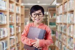 La bambina divertente tiene la letteratura nella biblioteca Fotografie Stock