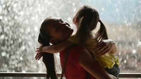La bambina dolce è abbracciante e baciante la sua bella giovane mamma Buona Festa della Mamma! La cascata è su fondo famiglia video d archivio