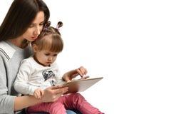 La bambina e la sua bella giovane mamma stanno utilizzando una compressa digitale immagini stock