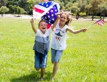La bambina ed il ragazzo adorabili funzionano sulla bandiera americana verde intenso della tenuta dell'erba all'aperto il bello g Immagini Stock