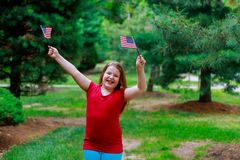 La bambina elementare felice dell'età sorride mentre tiene la bandiera americana nella sua iarda anteriore sul quarto di luglio F Immagini Stock