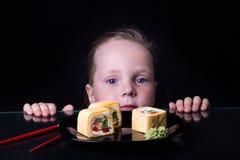 La bambina esamina i rotoli su un piatto Immagini Stock Libere da Diritti