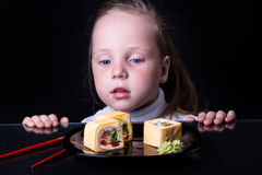 La bambina esamina i rotoli su un piatto Fotografia Stock Libera da Diritti