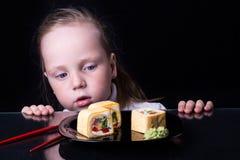 La bambina esamina i rotoli su un piatto Fotografia Stock
