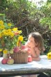 La bambina esamina un mazzo dei fiori immagini stock