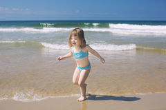 La bambina esegue il gioco con le onde sulla spiaggia Immagine Stock