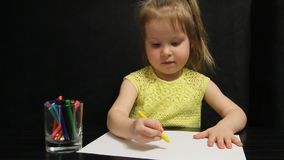 La bambina estrae il sole su carta con una matita gialla stock footage