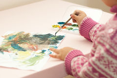 La bambina estrae le pitture su un foglio di carta Immagini Stock