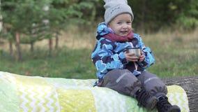 La bambina felice beve il tè nel parco fotografia stock libera da diritti