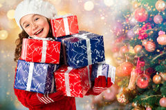 La bambina felice con molti regali si avvicina all'albero di Natale Immagine Stock Libera da Diritti