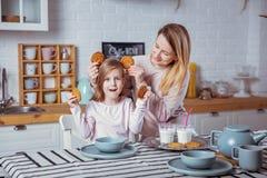 La bambina felice e la sua bella giovane madre hanno insieme prima colazione in una cucina bianca Sono divertentesi e giocanti co fotografia stock