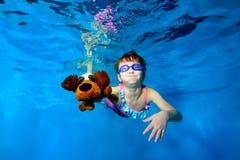La bambina felice nuota underwater nello stagno, giudicando un cane di piccola taglia disponibile, esaminando la macchina fotogra fotografie stock