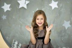 La bambina felice si siede su una luna gialla Sogni dolci immagini stock