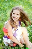 La bambina felice sta sedendosi sull'erba fotografia stock libera da diritti