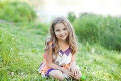 La bambina felice sta sedendosi sull'erba immagine stock libera da diritti