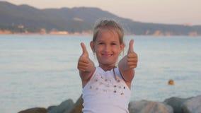 La bambina felice sulla spiaggia, bambina mostra il gesto eccellente La mano della ragazza con il pollice sul simbolo perfetto è  archivi video