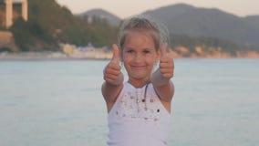 La bambina felice sulla spiaggia, bambina mostra il gesto eccellente La mano della ragazza con il pollice sul simbolo perfetto è  video d archivio