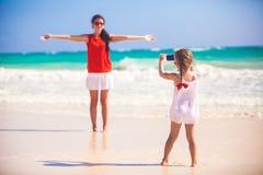 La bambina fotografa sua madre sulla spiaggia fotografia stock libera da diritti