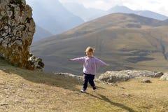 La bambina funziona allegro nelle montagne, sorridenti ed allunganti le sue mani fotografia stock