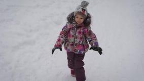 La bambina funziona su un sentiero per pedoni della foresta che dell'inverno il bambino è vestito calorosamente ed il tempo nel l stock footage