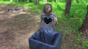 La bambina getta l'immondizia nel parco nel contenitore