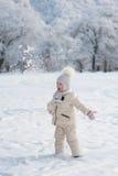 La bambina getta la neve ed il lancio su delle sue mani Immagini Stock