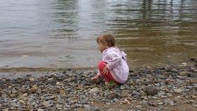La bambina getta le pietre nel fiume a terra stock footage