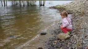 La bambina getta le pietre nel fiume a terra archivi video