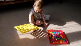 La bambina gioca delle capacit? motorie di sviluppo, raccoglie un mosaico multicolore per i bambini, lo sviluppo del progettista  archivi video