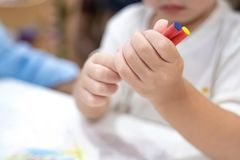 La bambina gioca ed impara al pastello di coloritura sulla carta nel ristorante del gelato , Bangkok, Tailandia fotografie stock
