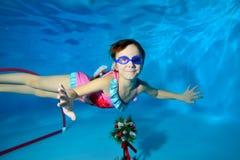 La bambina gioca gli sport, nuota underwater nello stagno, diffusione largamente le sue armi al lato, esaminante la macchina foto fotografia stock libera da diritti