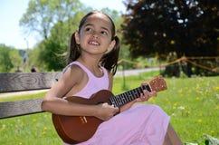 La bambina gioca il ukulele Fotografia Stock