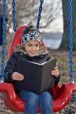 La bambina gode di di leggere Fotografie Stock