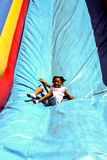 La bambina gode di di fare scorrere giù uno scivolo gonfiabile fotografie stock
