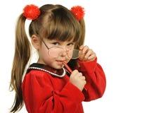 La bambina in grandi vetri e con la penna Immagini Stock Libere da Diritti