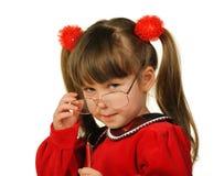 La bambina in grandi vetri e con la penna Fotografie Stock Libere da Diritti