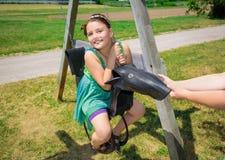 La bambina graziosa che si siede sulla vecchia gomma fatta oscilla in parco e nel godere del suo tempo libero Immagini Stock