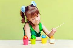La bambina graziosa dipinge le uova Fotografia Stock Libera da Diritti